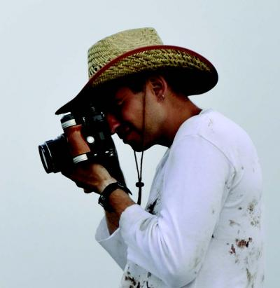 Portrait of Oded Hirsch wearing a hat and looking through a camera